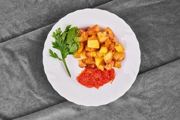 Gebakken aardappelen met tomatenpuree en kruiden.