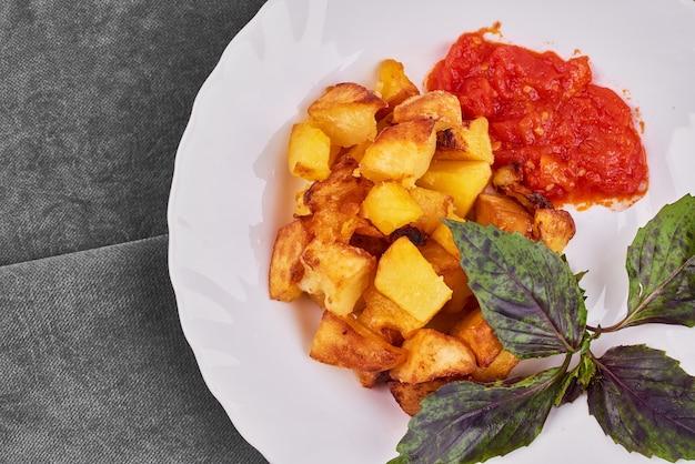 Gebakken aardappelen met tomatensaus en basilicum.