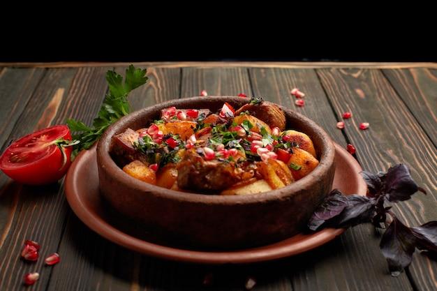 Gebakken aardappelen met vlees en granaatappel zaden, in een kleiplaat, op een houten achtergrond met kruiden en tomaat