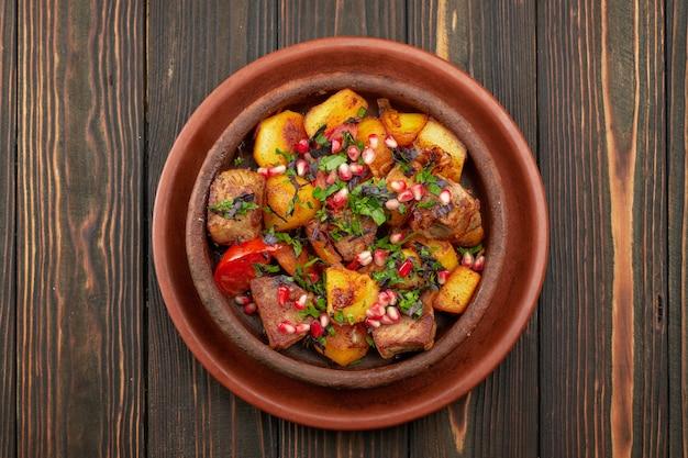 Gebakken aardappelen met vlees en granaatappel zaden, in een kleiplaat, op een houten achtergrond