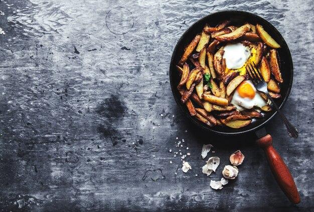 Gebakken aardappelen met vlees, ham en eieren in een pan close-up. horizontaal