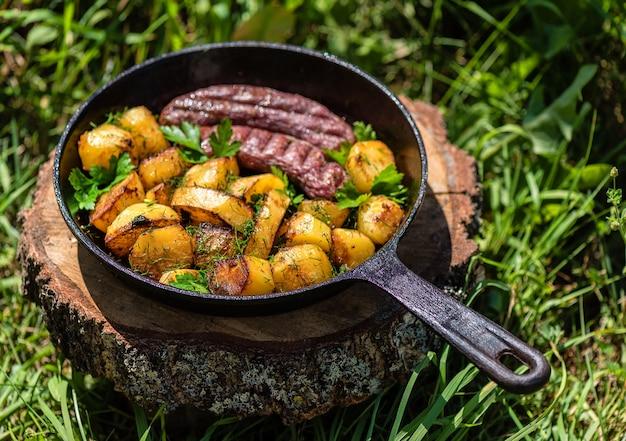 Gebakken aardappelen met vleesworst in een gietijzeren koekenpan