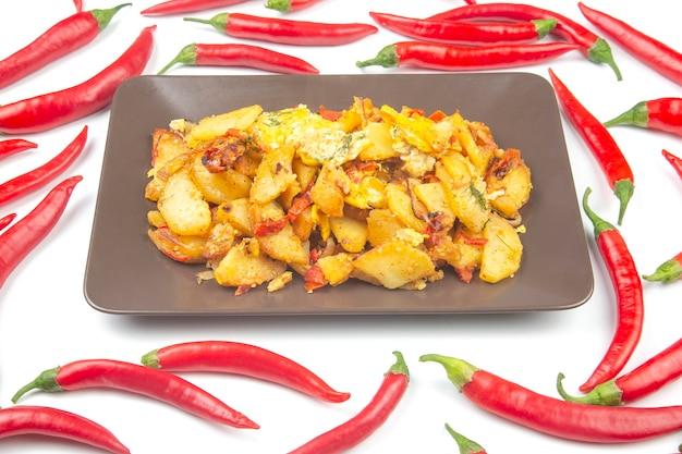 Gebakken aardappelen op een plaat op een wit oppervlak van rode peper