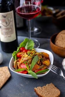 Gebakken aardappelen samen met verse groentesalade en rode wijn op grijze bureau