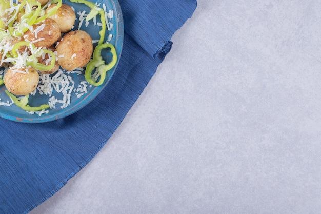 Gebakken aardappelen versierd met kaas en peper op blauw bord.