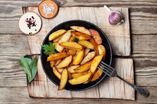 Gebakken aardappelen wiggen in een pan op houten tafel. bovenaanzicht.