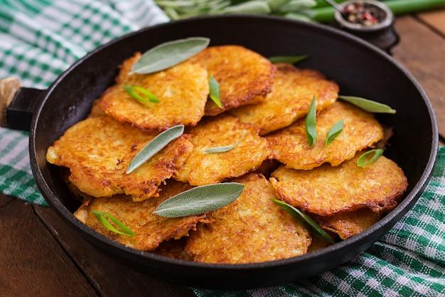 Gebakken aardappelpannenkoekjes in een pan op een houten tafel