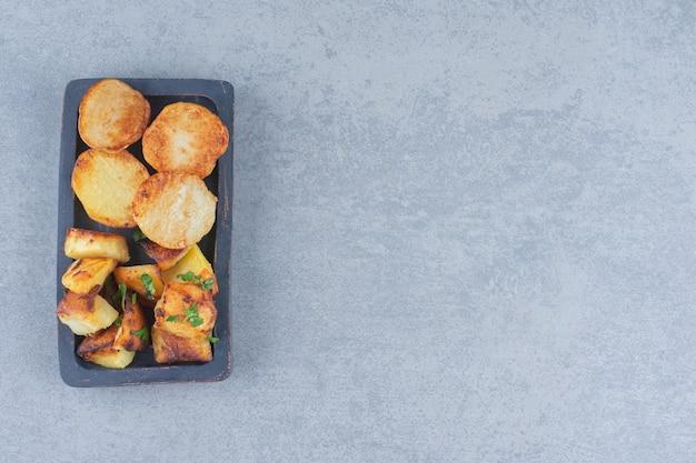 Gebakken aardappelpartjes. fastfood op zwarte houten plaat.