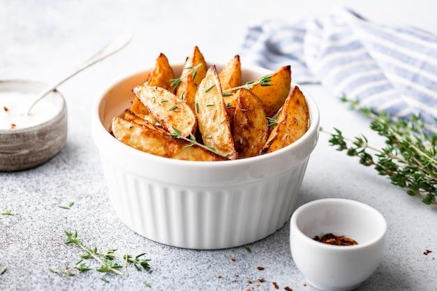 Gebakken aardappelpartjes met saus op een lichte ondergrond