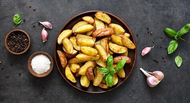 Gebakken aardappelpartjes met zout en knoflook in een bord op een zwarte achtergrond. uitzicht van boven.