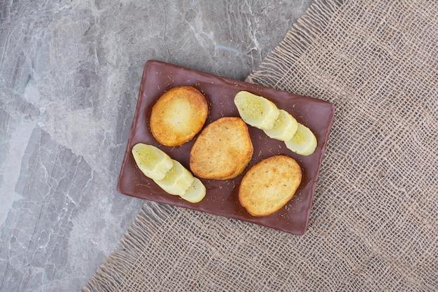 Gebakken aardappelschijfjes en ingelegde komkommers op plaat. hoge kwaliteit foto