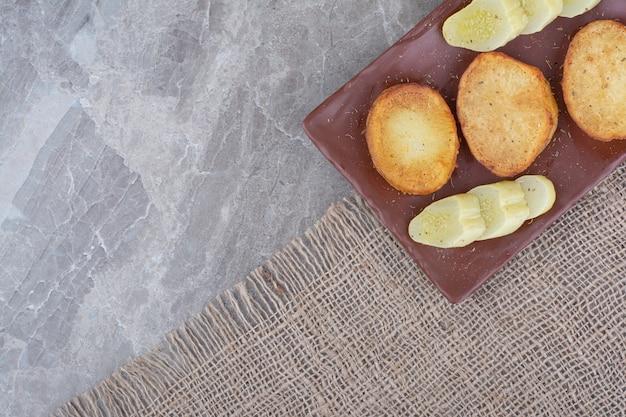 Gebakken aardappelschijfjes en ingelegde komkommers op plaat.