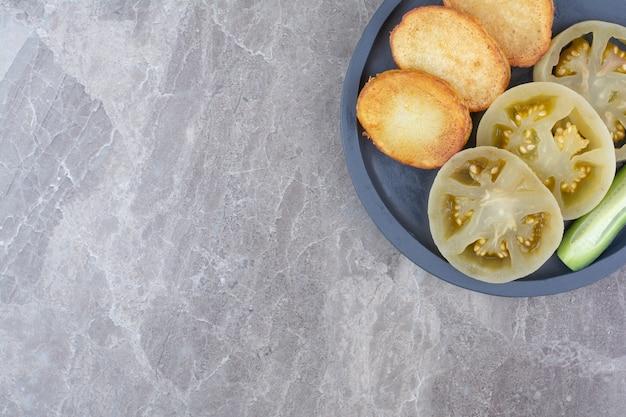 Gebakken aardappelschijfjes en ingelegde tomaten op plaat.