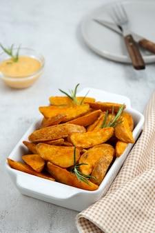 Gebakken aardappeltjes met kruiden en saus. gouden geroosterde aardappelen, heldere voedselfoto.