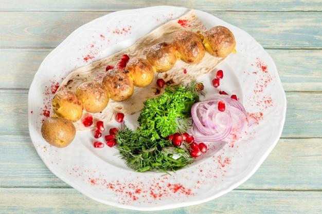 Gebakken aardappeltjes met ui, granaatappel en groen