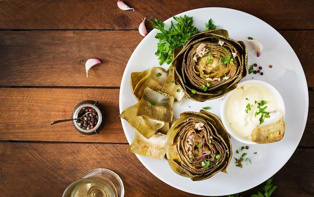 Gebakken artisjokken gekookt met knoflooksaus, mosterd en peterselie. bovenaanzicht