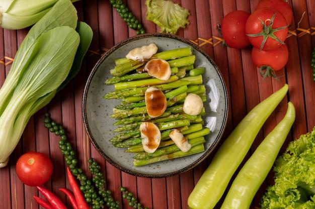 Gebakken asperges met oestersaus in een bord met paprika