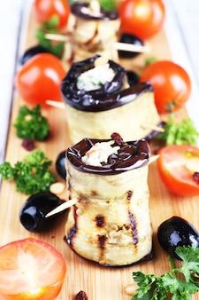 Gebakken aubergine met kwark en peterselie in een snijplank op een servet