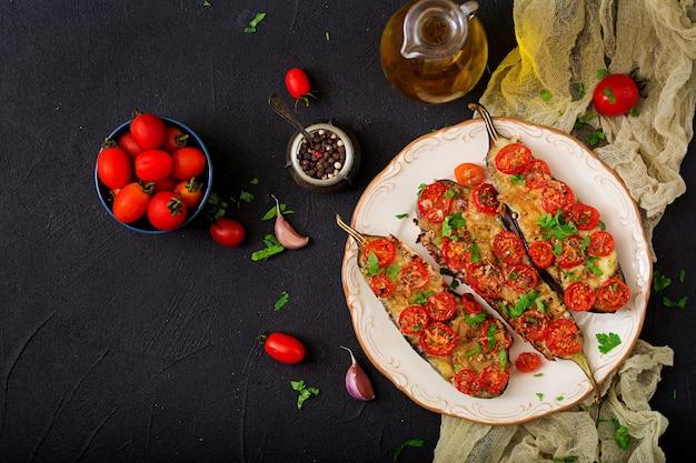 Gebakken aubergines met mozzarella en tomaten met italiaanse kruiden. plat leggen. bovenaanzicht