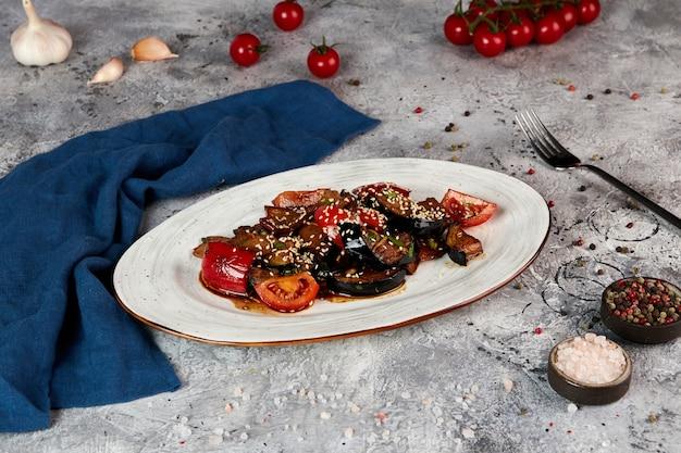 Gebakken auberginesalade met rundvlees en tomaten, grijze achtergrond