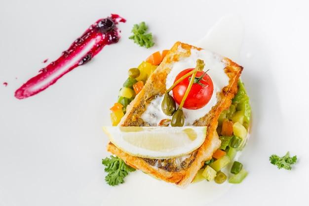 Gebakken baarsfilet met tomaat, citroen en groenten op witte plaat.