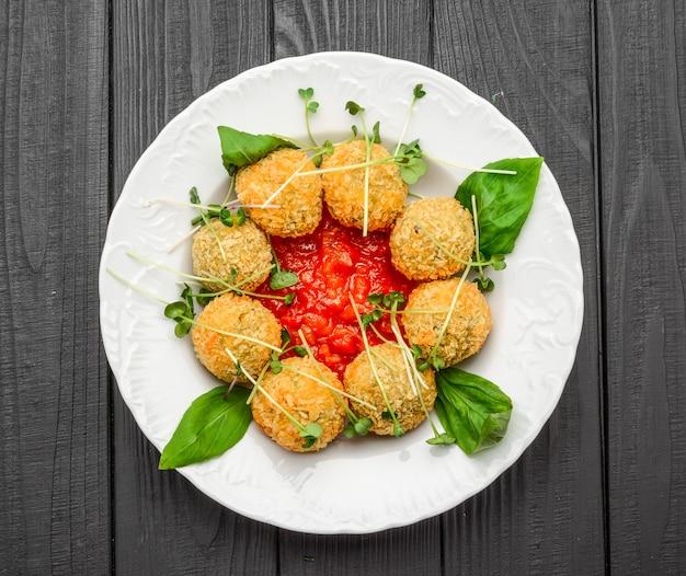 Gebakken balletjes met groenten en saus op een bord