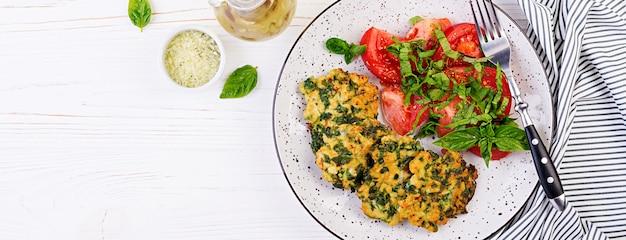 Gebakken biefstuk gehakte kipfilet met spinazie en een bijgerecht van tomatensalade. europese keuken. dieetvoeding. bovenaanzicht