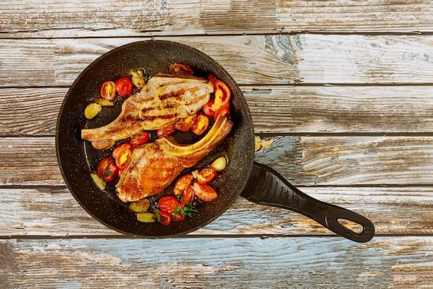 Gebakken biefstuk met tomaat en knoflook in de pan
