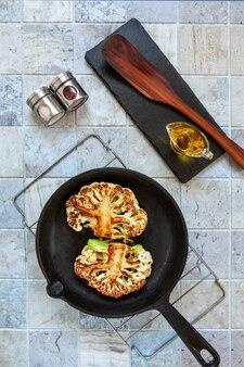 Gebakken biefstuk van verse bloemkool in een pan. een tussenfase van voorbereiding.