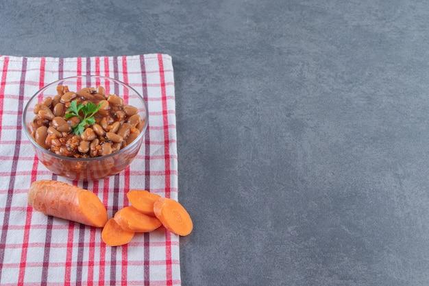 Gebakken bonen in een glazen kom naast gesneden wortel op een theedoek, op de blauwe achtergrond.