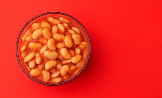 Gebakken bonen in tomatensaus geïsoleerd op rood