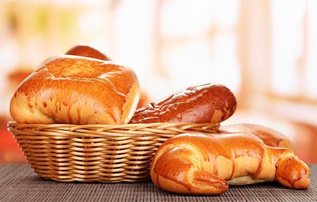 Gebakken brood in rieten mand op vensterachtergrond