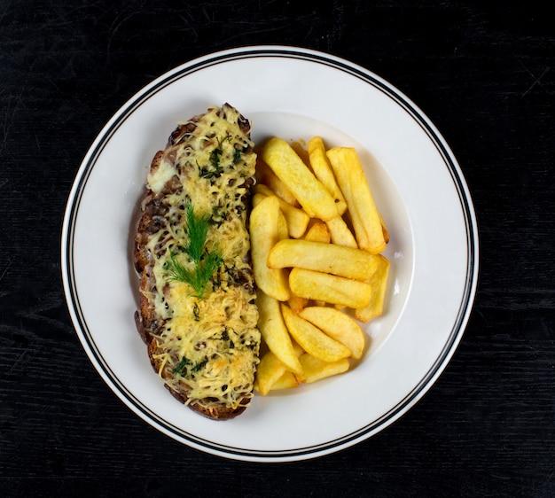 Gebakken brood met champignons en geraspte kaas met frietjes
