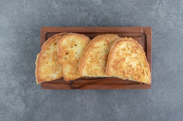 Gebakken brood met ei op een houten bord.