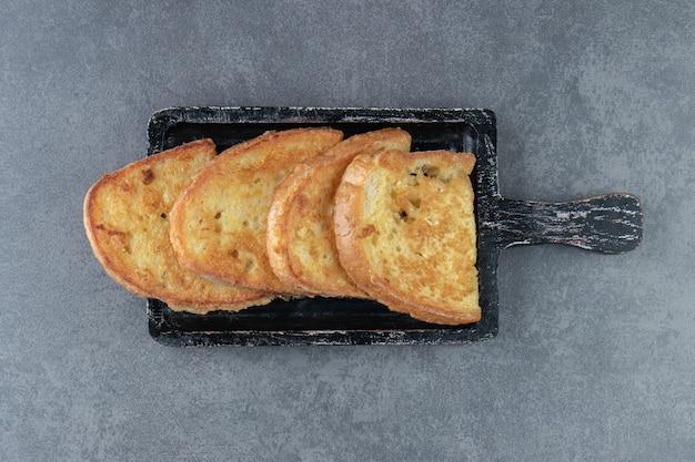 Gebakken brood met ei op zwart bord.
