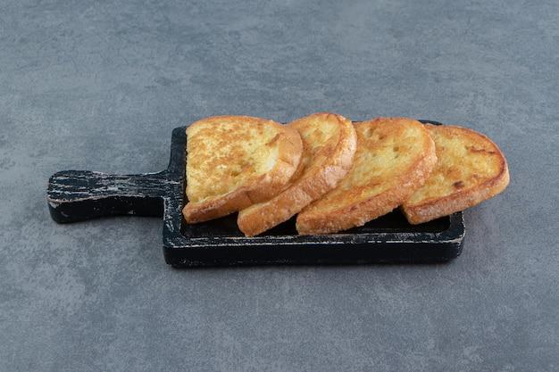 Gebakken brood met ei op zwart bord