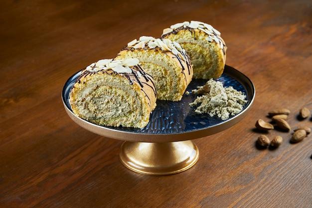 Gebakken broodjes met halva en amandelen op een blauw bord op een houten tafel. turkse zoetigheden. thee of koffie bakken