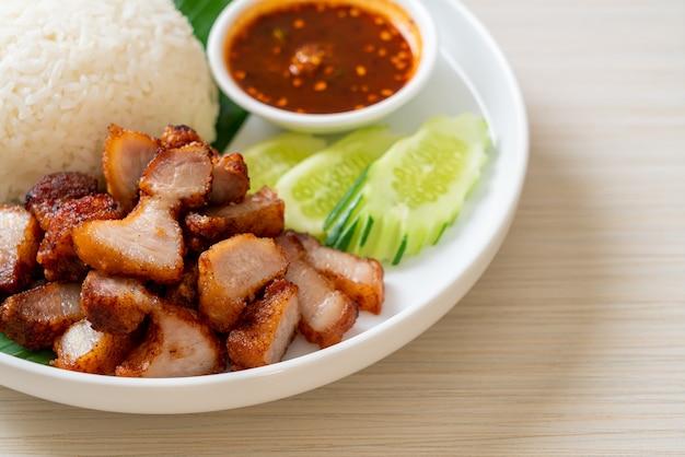 Gebakken buikspek met rijst met pikante saus op aziatische wijze