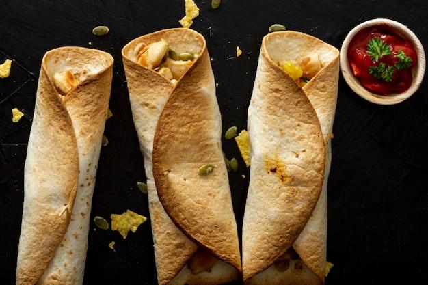Gebakken burrito's met kip en rode saus in kop