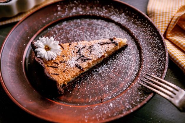 Gebakken cake in een keramische vorm bestrooid met plakjes chocolade op een houten tafel. plakje cake gelegd op kleiplaat en versierd met bloem