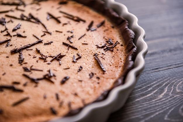 Gebakken cake in een keramische vorm bestrooid met plakjes chocolade op een houten tafel.