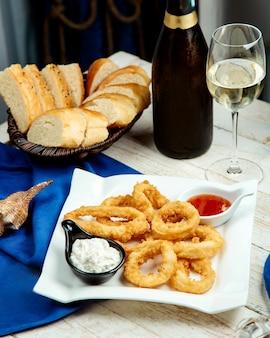 Gebakken calamares geserveerd met mayonaise en zoete chilisaus, witte wijn en brood