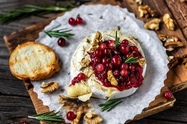 Gebakken camembert met cranberrysaus, stokbrood en rozemarijn op rustieke houten tafel.