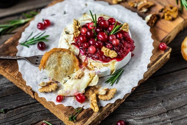 Gebakken camembertbrie met verse rozemarijn en cranberrysaus. gastronomisch voorgerecht.