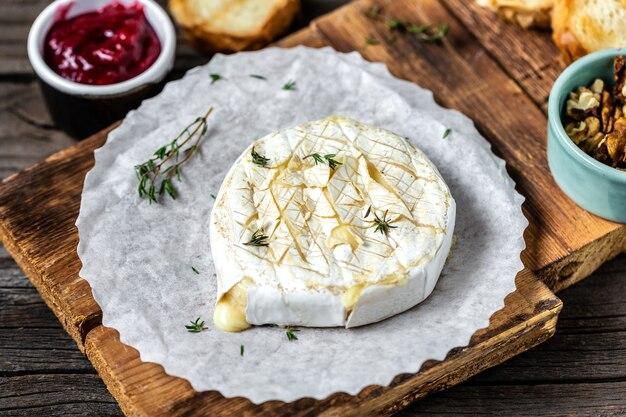 Gebakken camembertkaas met geroosterde sneetjes brood, tijm, veenbessen en noten. traditionele franse kaas.