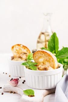 Gebakken champignon julienne met kip, kaas en toast in kommen