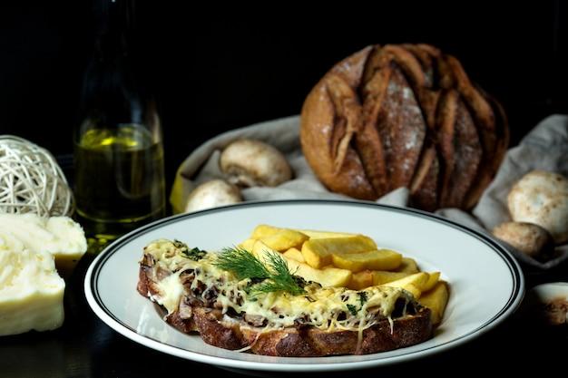 Gebakken champignons bedekt met gesmolten kaas op bruine toast, geserveerd met friet