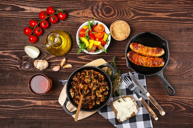 Gebakken champignons en worst in ijzeren koekepan. ingrediënten voor rustieke eenvoudige gerechten, weergave van bovenaf.