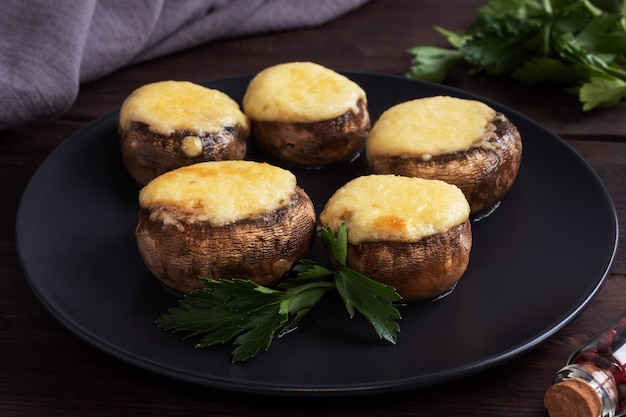 Gebakken champignons gevuld met kaas en kruiden op een zwarte plaat. houten achtergrond.