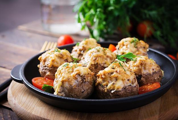 Gebakken champignons gevuld met kipgehakt, kaas en kruiden op een houten ondergrond